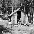 William C. Noble, fire observer, sitting in the doorway of his cabin. Photo: Courtesy of the New York State Archives